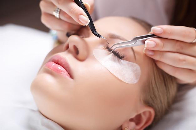まつげエクステンション手順。長いまつげの女性の目。まつげ、クローズアップ、選択したフォーカス。 Premium写真