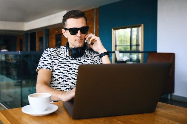 サングラスの若いハンサムな流行に敏感な男は、カフェテリアで携帯電話を話しているラップトップを使用しています。 Premium写真