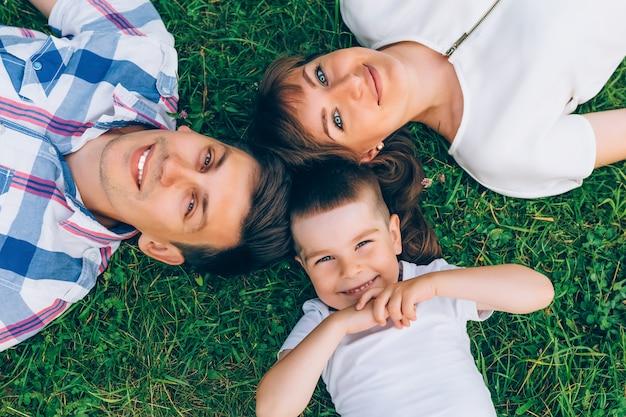 Жизнерадостная семья лежа на траве в круге и смотря камеру. Premium Фотографии