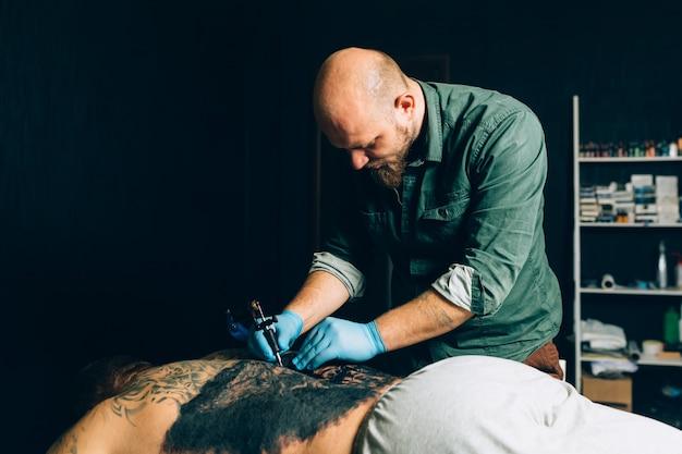 Тату мастер делает татуировку. крупный план Premium Фотографии