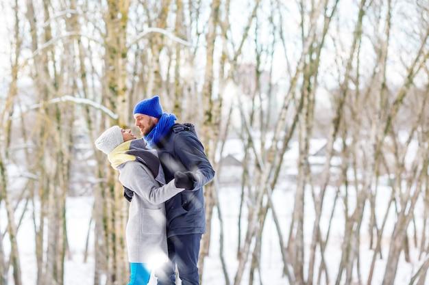 笑って、楽しんで冬の公園で幸せな若いカップル。家族のアウトドア。 Premium写真
