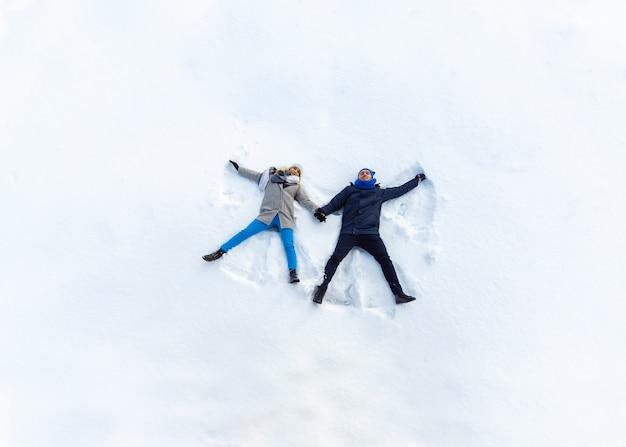 雪の上に横たわる冬の公園で幸せな若いカップル。雪の天使を作る Premium写真