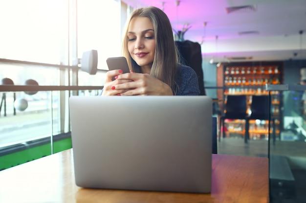 カフェでスマートフォンでテキストメッセージを入力する女性。 Premium写真