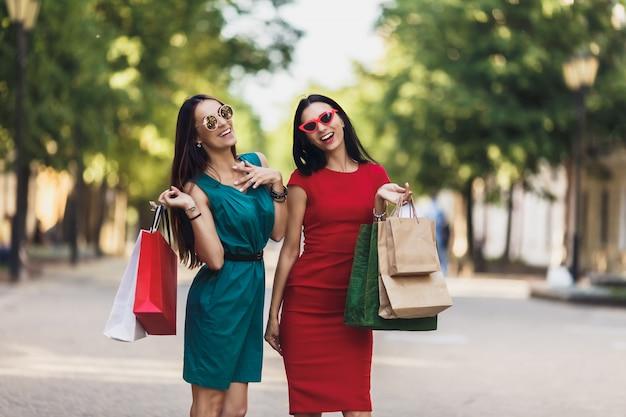 夏の街で買い物袋を持つ若い魅力的な女の子。サングラスと笑顔の美しい女性。肯定的な感情とショッピングの日の概念。 Premium写真
