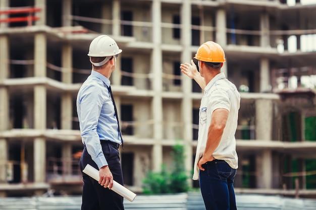 建築家と建設現場で議論するビルダー Premium写真
