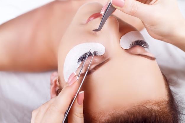 Процедура наращивания ресниц. женский глаз с длинными ресницами. ресницы со стразами. ресницы, крупный план Premium Фотографии