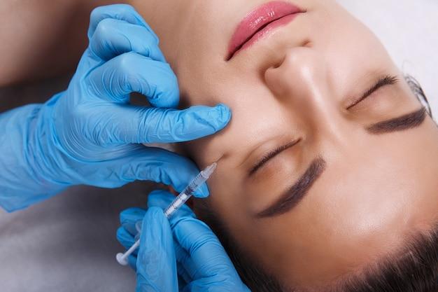 フェイシャルビューティーインジェクション。ヒアルロン酸注射を受ける美しい若い女性の肖像画。魅力的な女性の顔の近くの注射器を保持している手袋の手のクローズアップ。 Premium写真