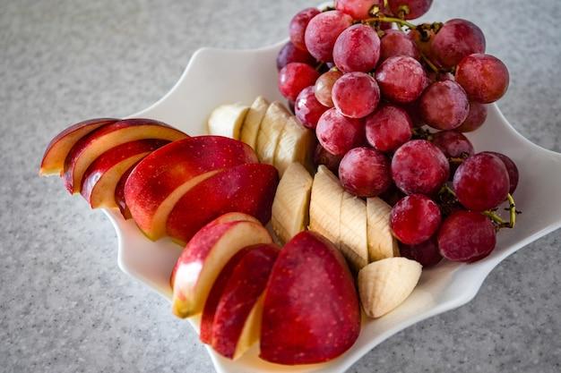 グレー、リンゴ、バナナ、ブドウのプレートにスライスされたフルーツ Premium写真