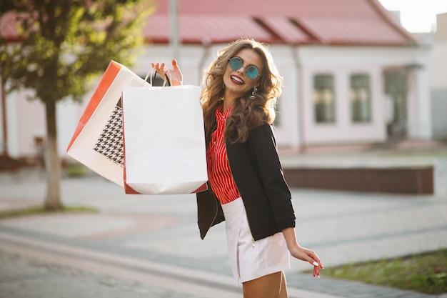 多くの紙袋で買い物をした後通りを歩いて肯定的な女性。 Premium写真