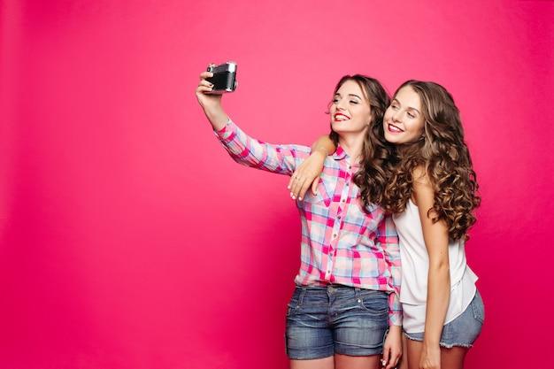 Очаровательные дружелюбные девушки, принимающие автопортрет через пленочную камеру. Premium Фотографии