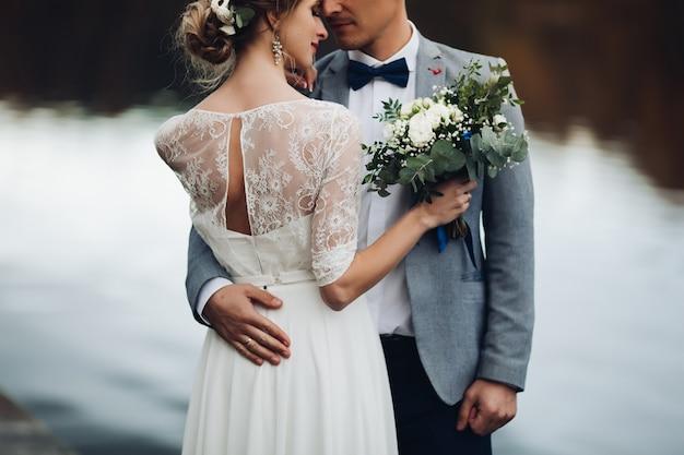 湖の近くのエレガントな新婚夫婦の作物 Premium写真