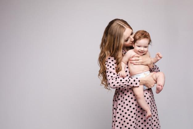 Молодая мать держит ребенка на руках и смеется Premium Фотографии