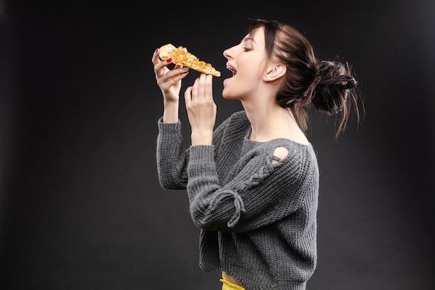 ピザを食べて口を開けて空腹の少女 Premium写真