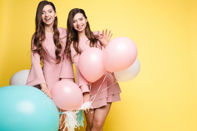 Симпатичные брюнетки-близнецы в розовых платьях на желтом фоне Premium Фотографии