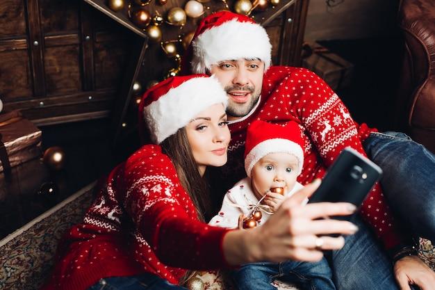 Прелестный ребенок с родителями, принимая селфи с мобильным телефоном Premium Фотографии