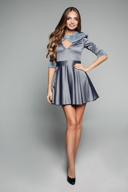 ファーの襟と袖が付いたファッショナブルなグレーのドレスを着たハッピーモデル。 Premium写真