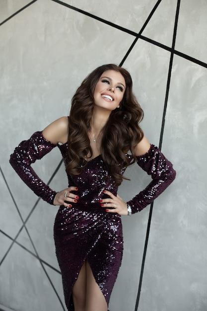 Великолепная брюнетка в сверкающем фиолетовом платье. Premium Фотографии