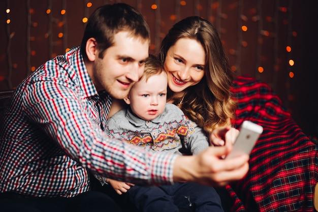 Положительная семья при маленький белокурый сын принимая фото в студии во время рождества. Premium Фотографии