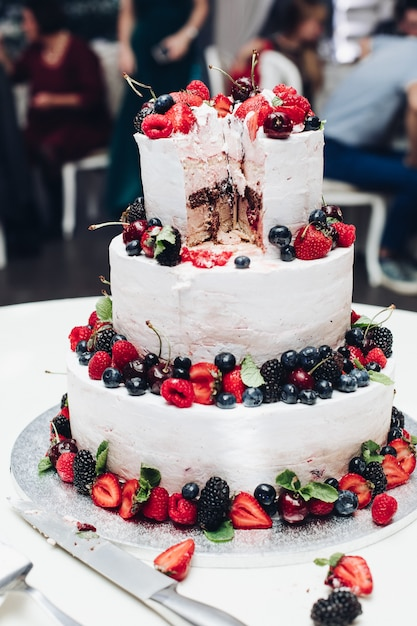新鮮なジューシーなベリーとフルーツで覆われた白いホイップクリームと大きな素晴らしい結婚式のおいしいケーキ Premium写真
