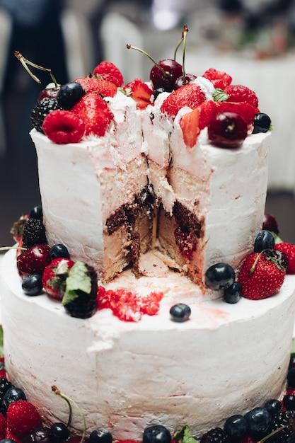 ベリーと美しいウェディングケーキ。クローズアップでウエディングケーキをスライスしました。 Premium写真
