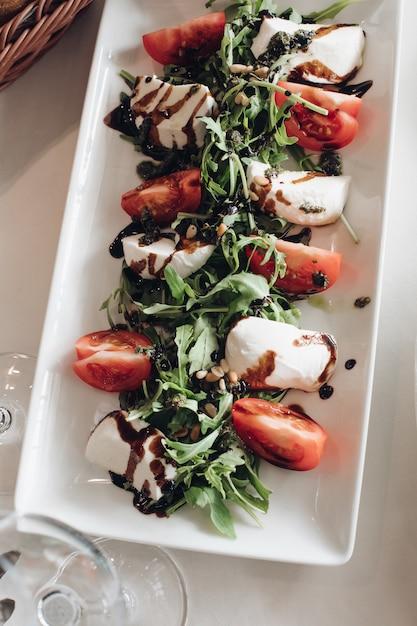 新鮮な野菜と緑のマスカルポーネのクローズアップ。バルサミコソースをトッピング。 Premium写真