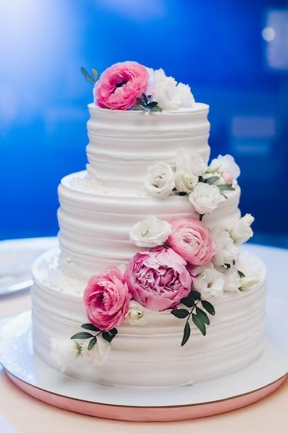 ホワイトクリームのアイシングで覆われた食欲をそそる新鮮なペストリーケーキとテーブルの上に役立つ甘い花を飾る Premium写真
