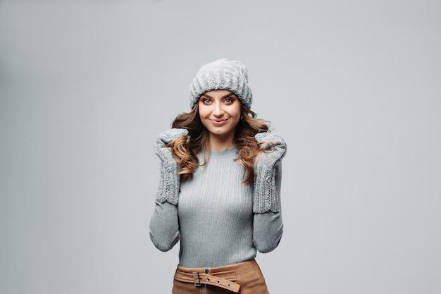 暖かい灰色の帽子とセーターで美しい笑顔の女の子。 Premium写真