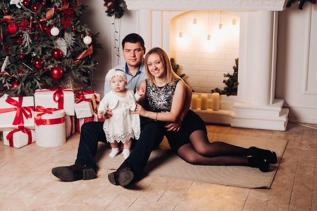 Родители, сидя на полу с ребенком возле елки. Premium Фотографии