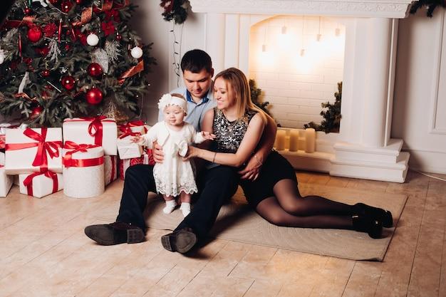 リビングルームでかわいい子と床に座って親。クリスマスツリー、キャンドル、ランプ、赤の弓と白いギフトボックスで飾られたアパート。白いドレスを着てかわいい女の子。 Premium写真