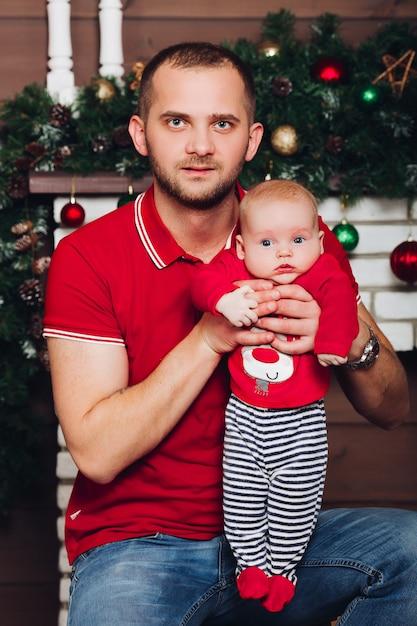 素敵で幸せな父親が幼い息子を手で抱き上げ、彼を起こします Premium写真