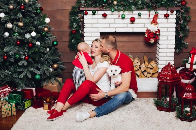 幼い息子とかわいい犬と暖炉のそばに座って、笑顔の幸せな家族 Premium写真