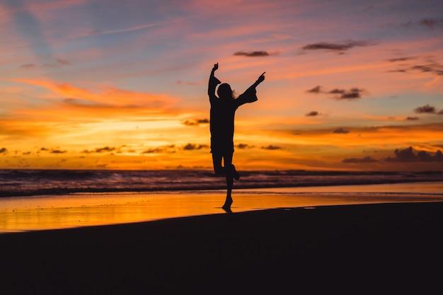 夕日のビーチにいる人たち。女の子は夕日を背景にして飛び降りています。 無料写真