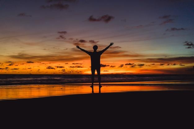 日没時に海岸の人々。人は夕日を背景にジャンプする 無料写真