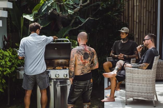屋外でバーベキューグリルを調理する友人の会社 無料写真