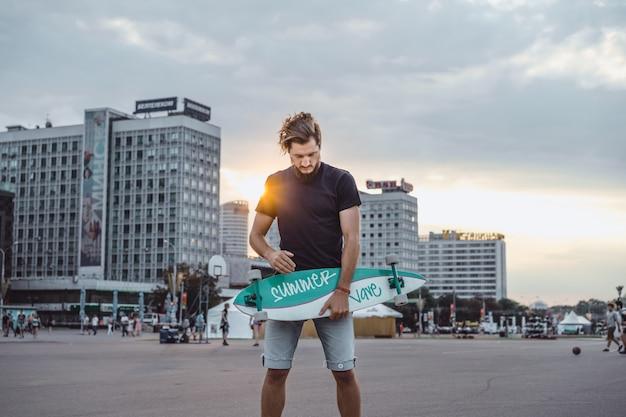 スケートボードを持つ男 無料写真