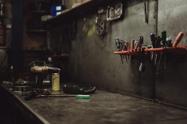Красивая девушка с длинными волосами в гараже, ремонт мотоцикла Бесплатные Фотографии