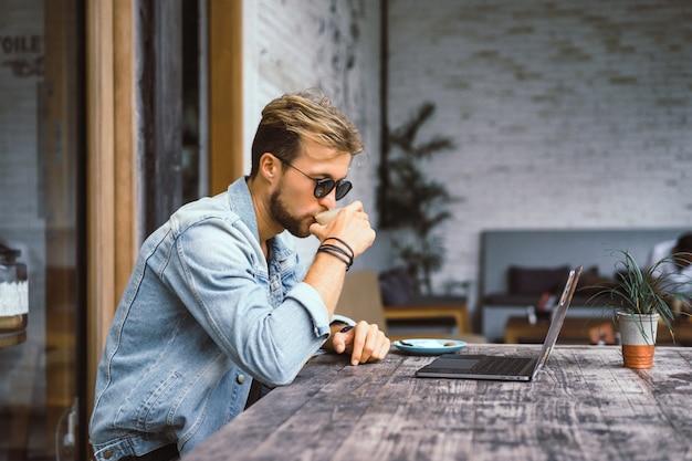 Молодой привлекательный деловой человек в кафе работает для ноутбука, пьет кофе. Бесплатные Фотографии