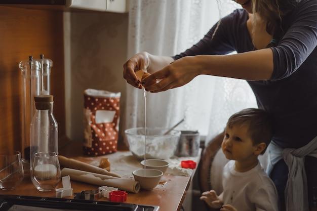 キッチンの小さな男の子は、お母さんが料理するのに役立ちます。子供は料理に関わっています。 無料写真