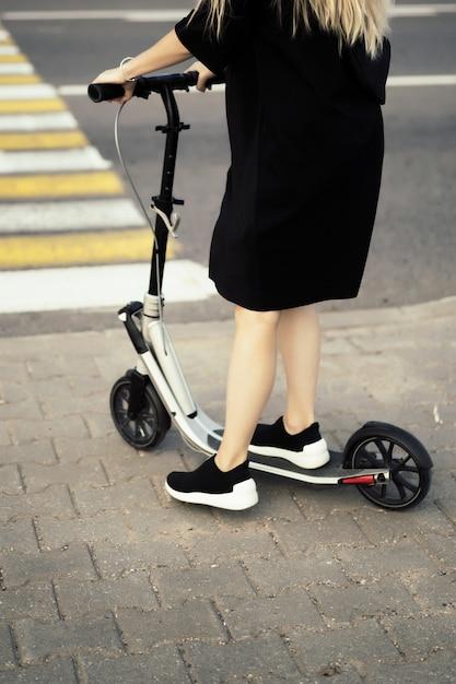 電動スクーターには長い毛を持つ若い女。電動スクーターの女の子。 無料写真
