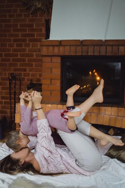 子供を持つ若い女性。ママと息子は暖炉のそばで楽しんで、浮気しています。 無料写真