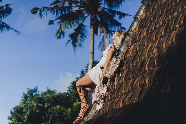 屋根の上のドレスの長いブロンドの髪を持つヒッピーの女の子。 無料写真
