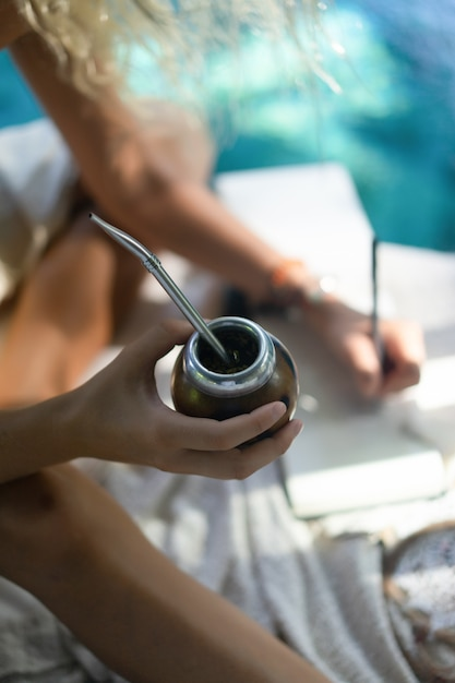 マテ茶を飲む屋根の上の長いブロンドの髪と美しいインドのヒッピーの女の子。 無料写真