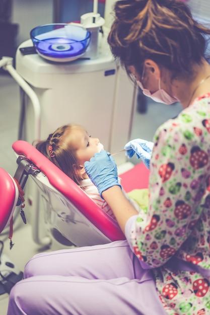 小児歯科医。歯科医の受付で小さな女の子。 無料写真