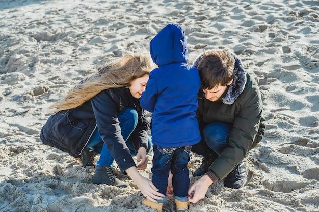 Молодая семья с детьми проводит выходные на берегах холодного балтийского моря Бесплатные Фотографии