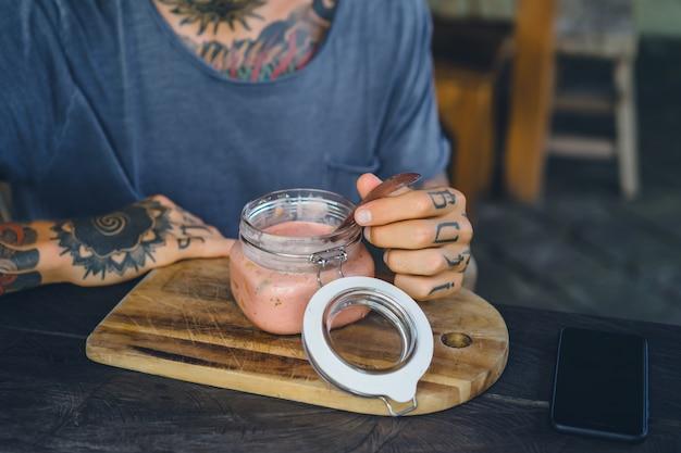 便利な朝食。美しい朝食のフィード、入れ墨の男性の手。 無料写真