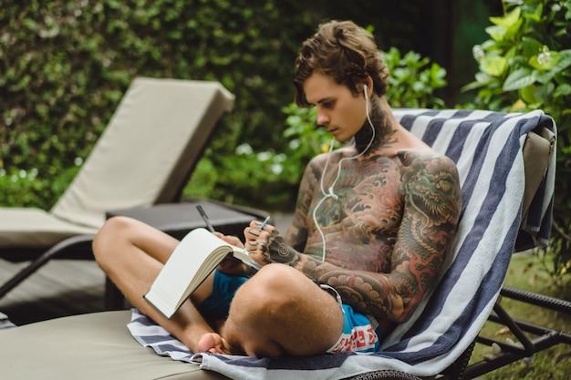 Молодой человек в татуировках в наушниках слушает музыку и рисует в блокноте. Бесплатные Фотографии