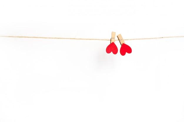 Сердца зажимок для белья вися на веревочке и изолированные на белизне. Premium Фотографии