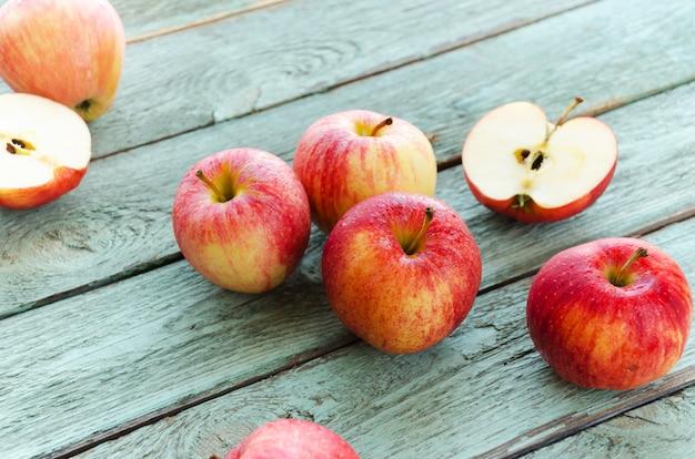 Красные яблоки на бирюзовом фоне деревянных. осенние дни. Premium Фотографии