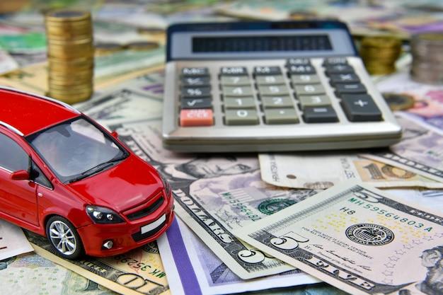 さまざまな国の通貨紙幣の電卓と赤いおもちゃの車。車の購入、レンタル、メンテナンスにかかる費用。 Premium写真