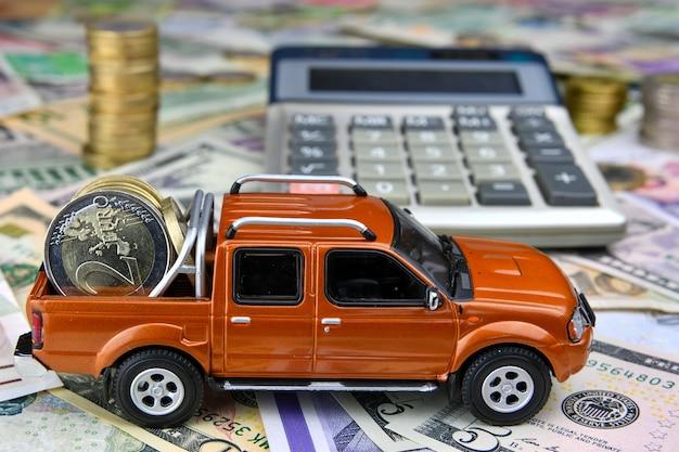 さまざまな国の通貨紙幣の貨物ボックスにコインを置いた電卓とピックアップのおもちゃの車。車の購入、レンタル、メンテナンスにかかる費用。 Premium写真